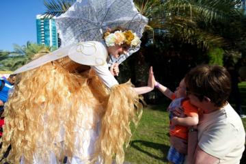 Helter Skelter family and community event gold fairy stilt walker high 5
