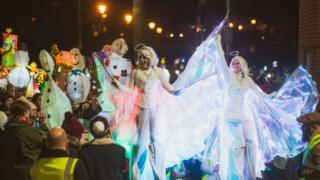 Stilt walkers as angels in parade
