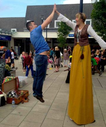 Medieval stilt walker high five
